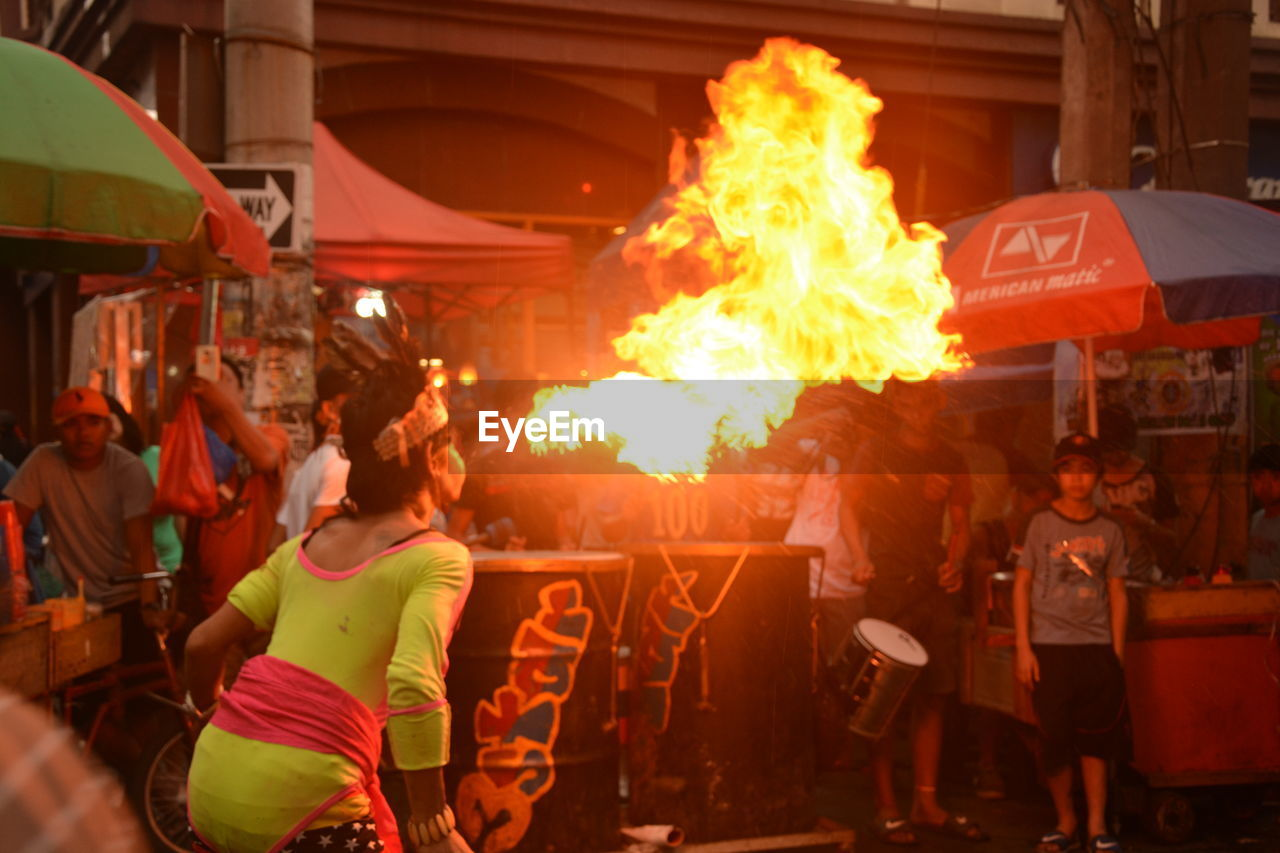 real people, group of people, burning, men, fire, flame, large group of people, heat - temperature, crowd, adult, women, lifestyles, fire - natural phenomenon, leisure activity, motion, occupation, architecture, standing, glowing