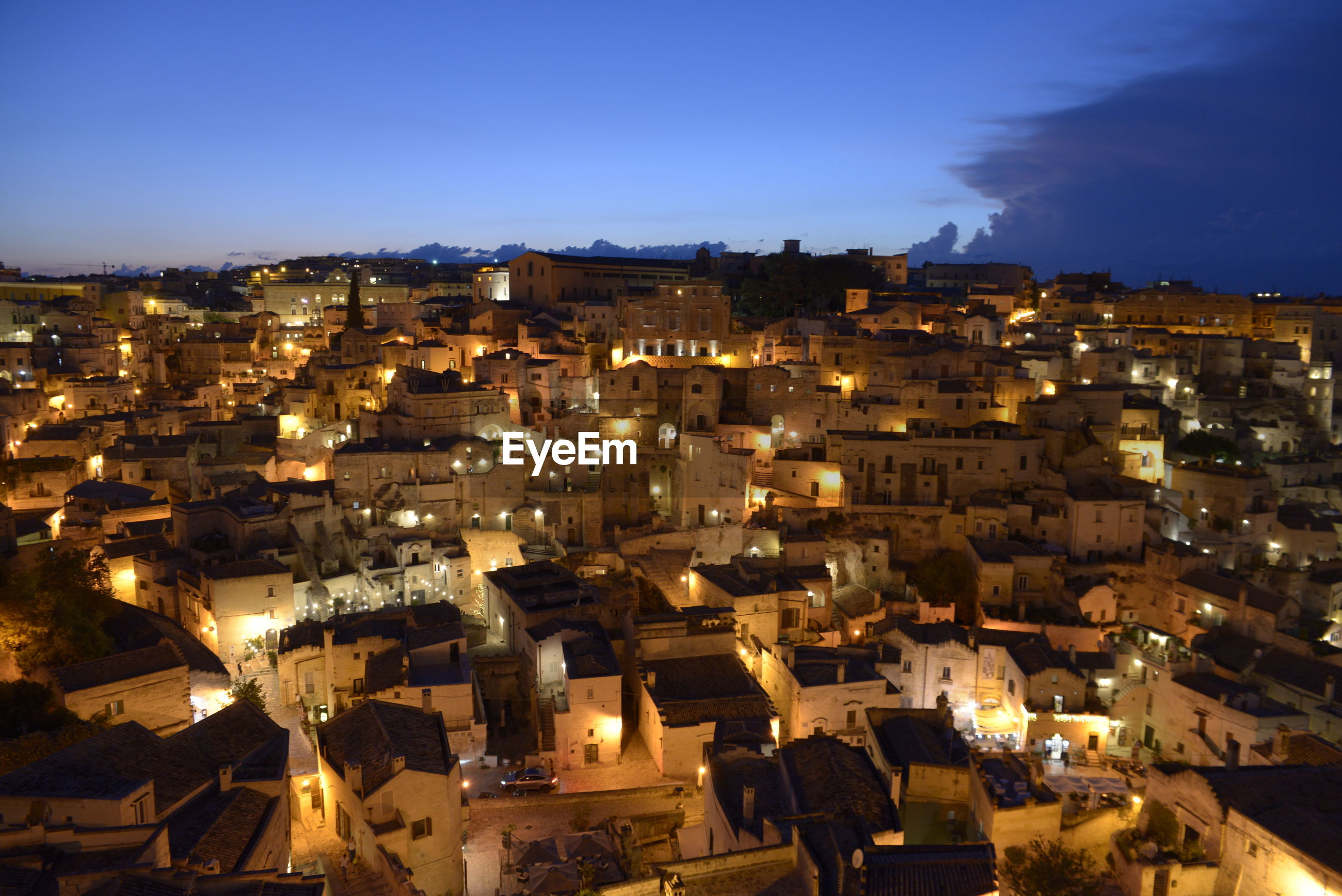 HIGH ANGLE VIEW OF ILLUMINATED TOWN AGAINST SKY