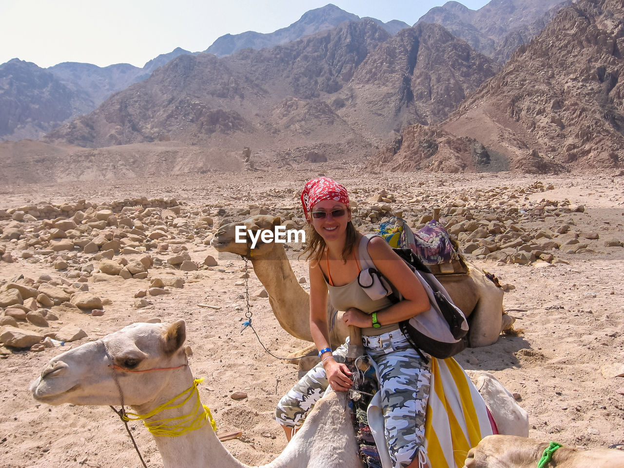 real people, young adult, young women, mountain, looking at camera, desert, front view, portrait, lifestyles, outdoors, day, leisure activity, one person, arid climate, nature, women, holding, smiling, mammal, sitting, domestic animals, adult, adults only, people