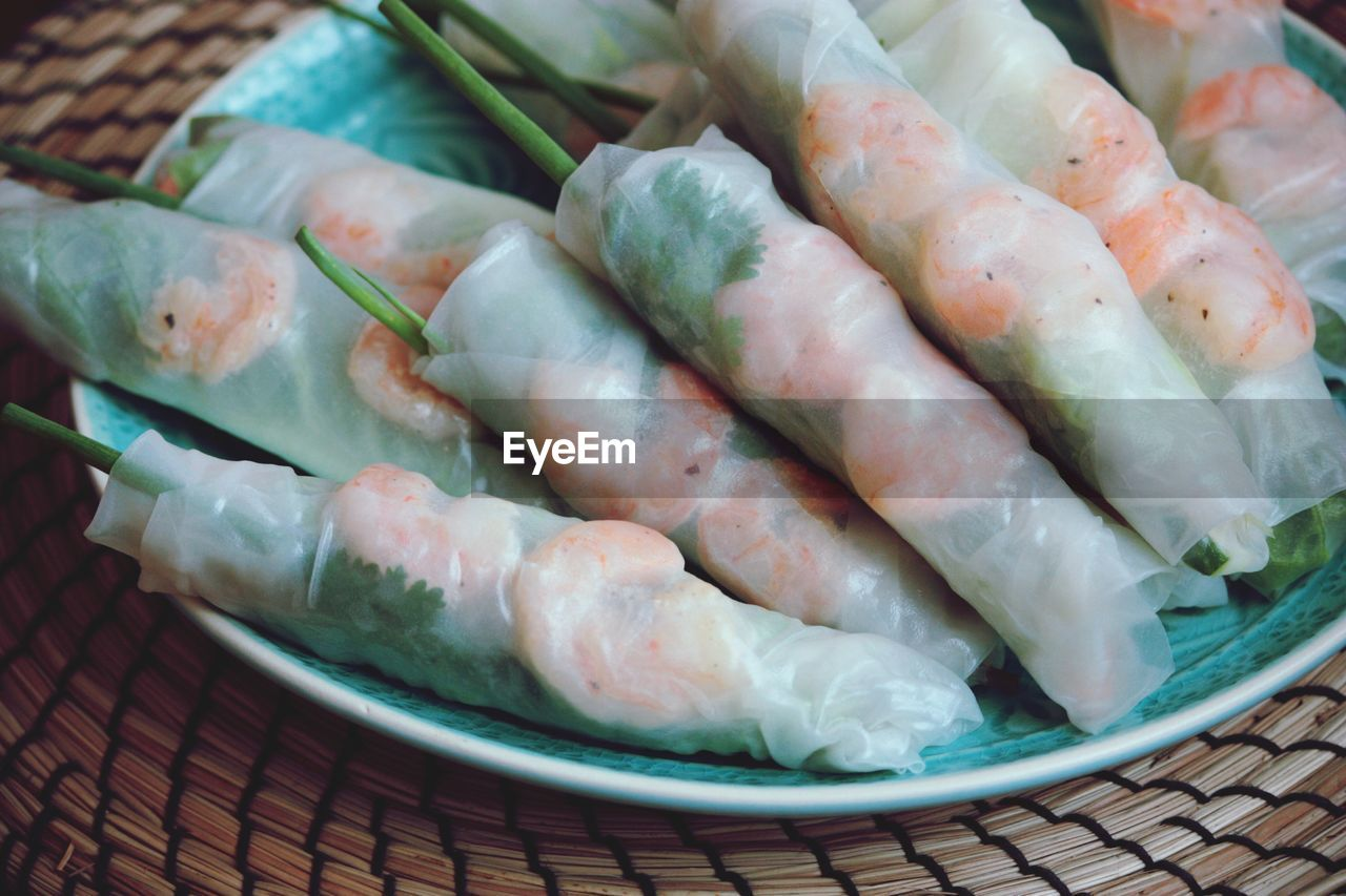 Close-up of uncooked spring rolls in plate