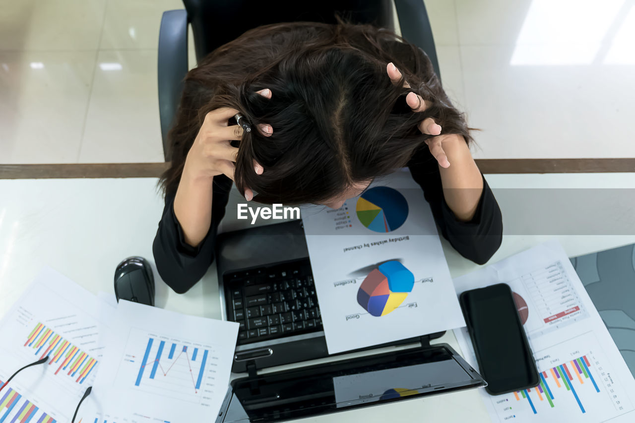 High angle view of woman analyzing charts by laptop at office desk