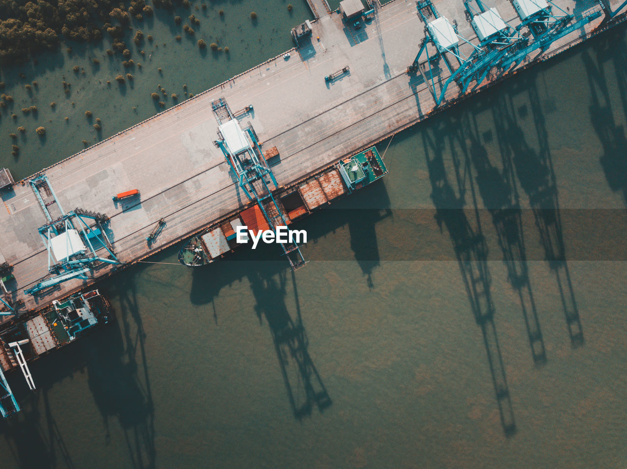 high angle view, day, no people, water, hanging, nature, clothing, built structure, outdoors, architecture, laundry, metal, industry, tilt, wood - material, sunlight, drying, pier, reflection