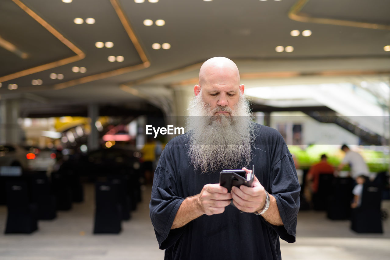 MAN USING MOBILE PHONE WHILE STANDING ON LAPTOP KEYBOARD