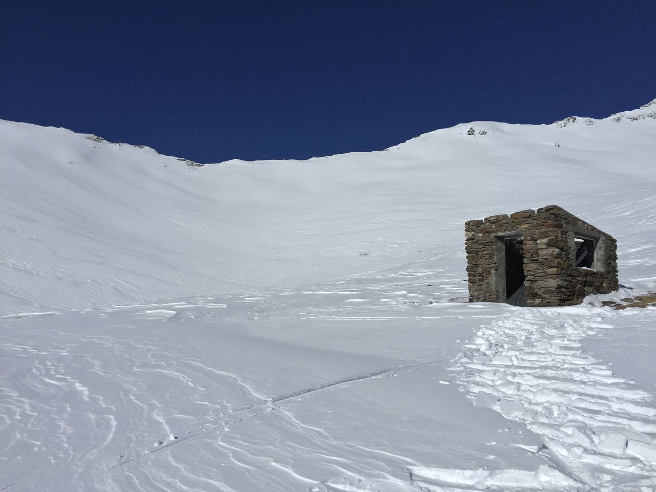 Low Angle View Of Abandoned House On Snowy Hill Against Sky