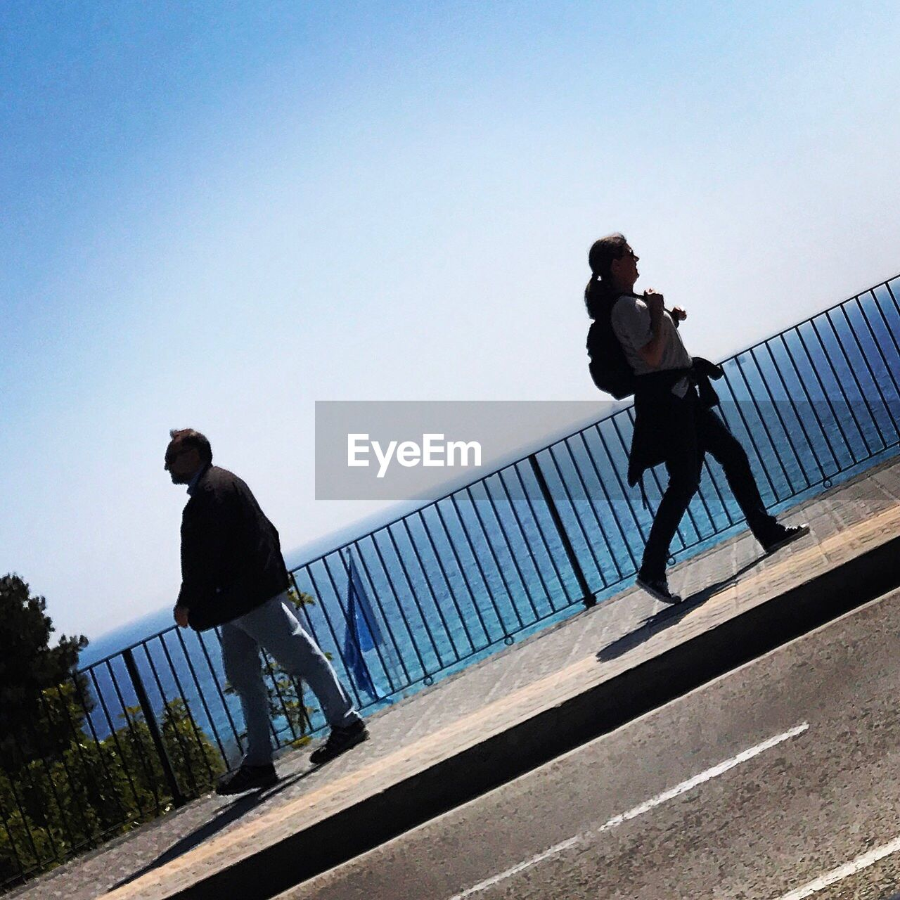 railing, full length, clear sky, day, real people, outdoors, lifestyles, men, leisure activity, low angle view, bridge - man made structure, two people, footbridge, friendship, sky, sportsman, people, adult