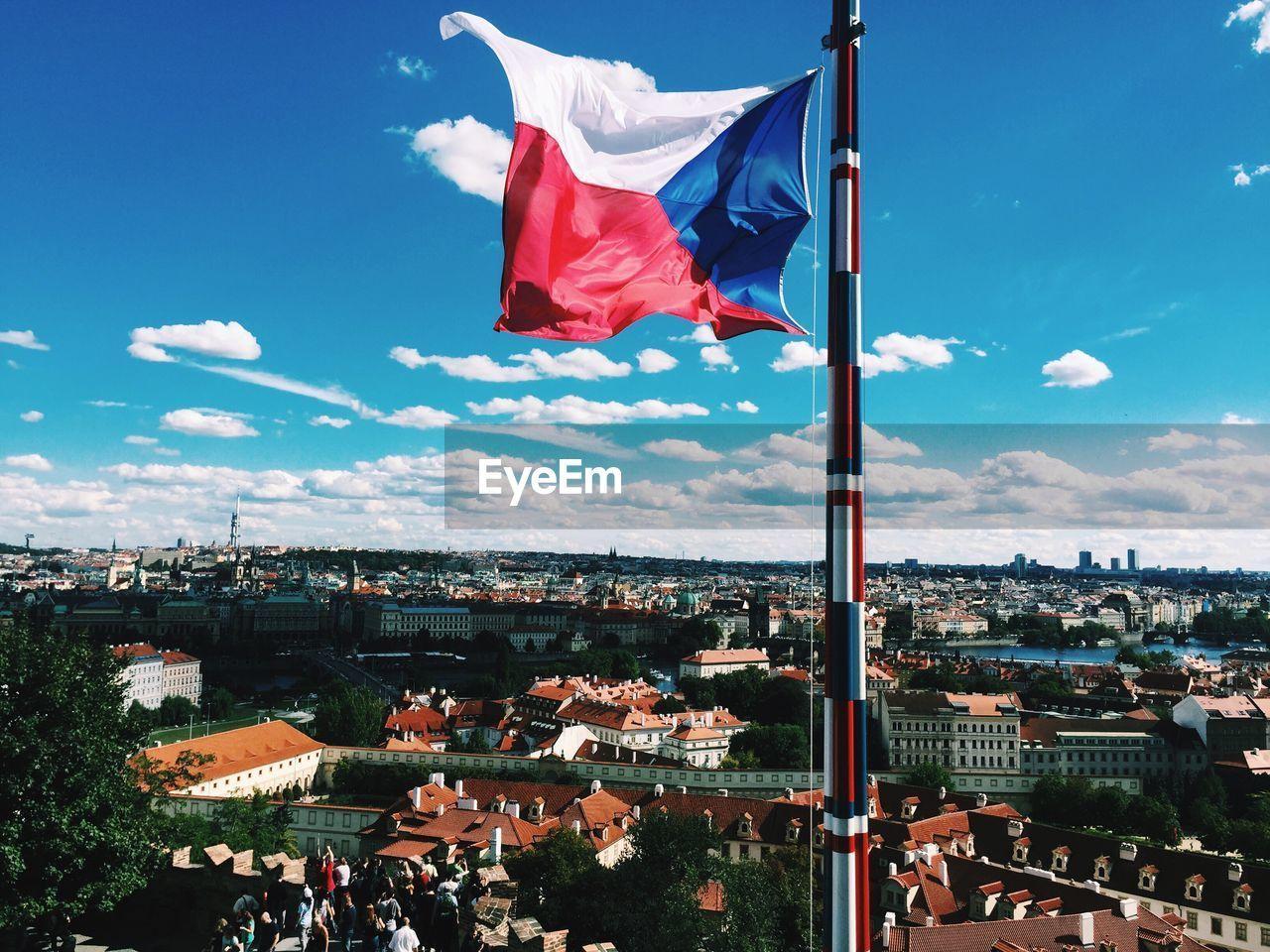 Czech flag waving by cityscape against sky