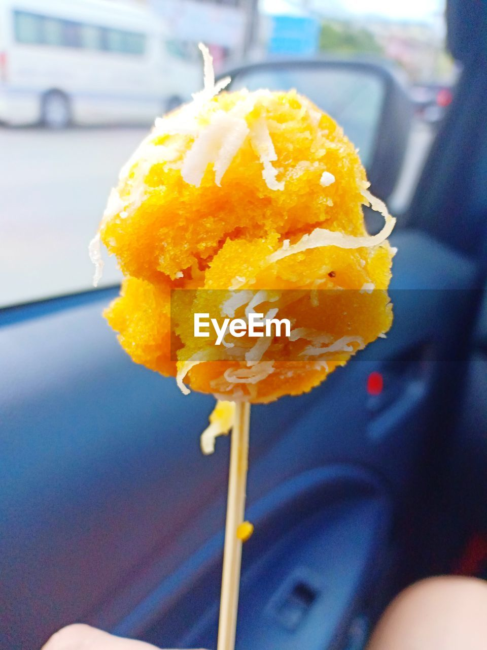 motor vehicle, car, yellow, mode of transportation, freshness, transportation, land vehicle, close-up, flower, focus on foreground, vehicle interior, flowering plant, food, food and drink, holding, one person, real people, sweet food, day, car interior, outdoors, flower head, temptation, snack