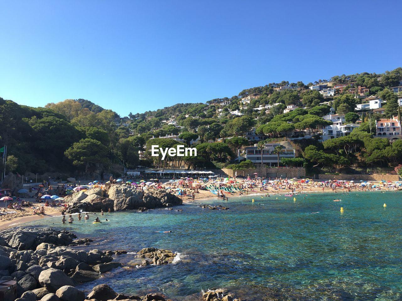 Tourist at costa brava against clear blue sky