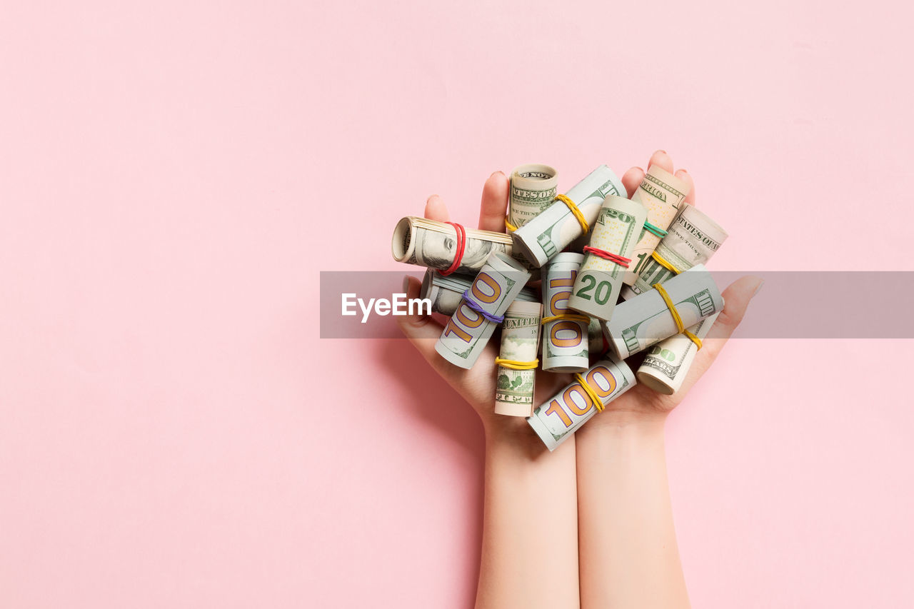 large group of objects, indoors, colored background, one person, studio shot, multi colored, currency, close-up, copy space, abundance, choice, human hand, human body part, pink background, variation, pink color, wealth, still life, finance, excess