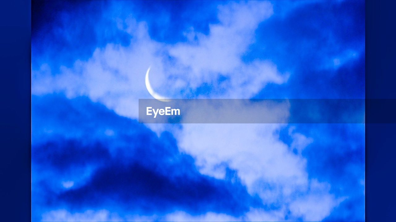 sky, cloud - sky, beauty in nature, blue, low angle view, nature, scenics, tranquility, outdoors, tranquil scene, moon, sky only, no people, day, crescent, astronomy