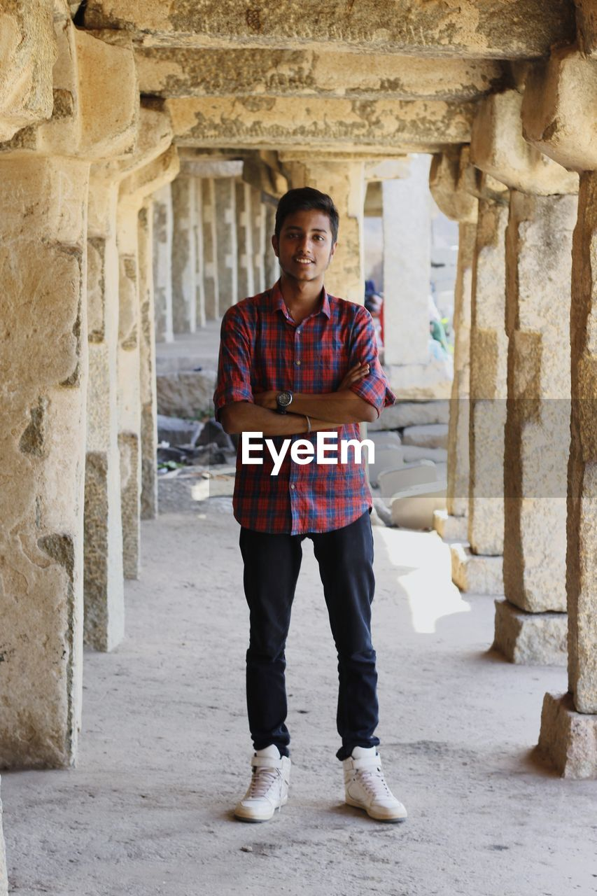 looking at camera, one person, portrait, architecture, standing, real people, built structure, front view, young adult, full length, the past, smiling, young men, day, history, casual clothing, confidence, building, architectural column, outdoors