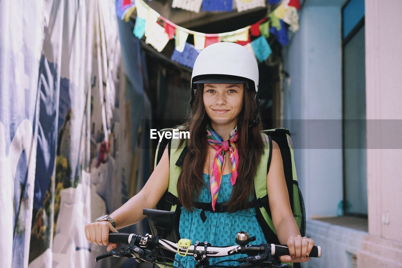 Portrait Of Smiling Woman With Bicycle On Alley