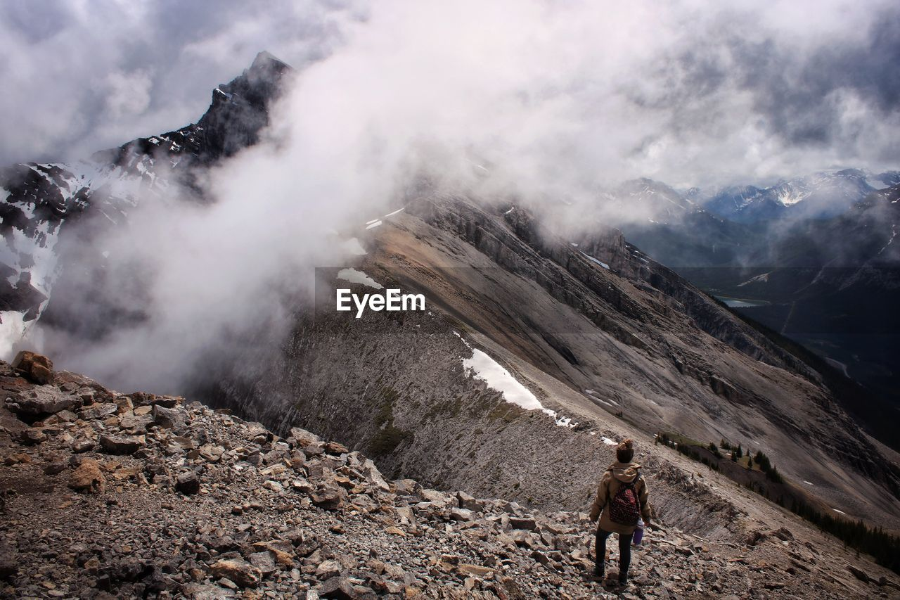 Scenic view of hiker and cloud covered mountains against sky