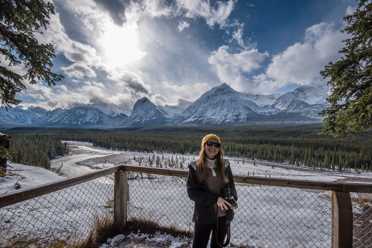Cheerful Woman With Camera Standing By Fence Against Mountains During Winter