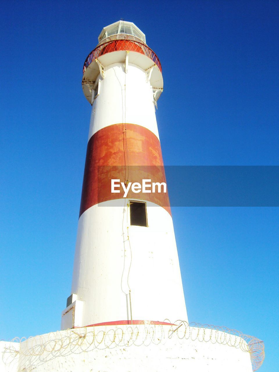 sky, low angle view, tower, lighthouse, built structure, architecture, guidance, clear sky, blue, building exterior, security, day, safety, nature, travel, sunlight, protection, no people, tall - high, building, outdoors
