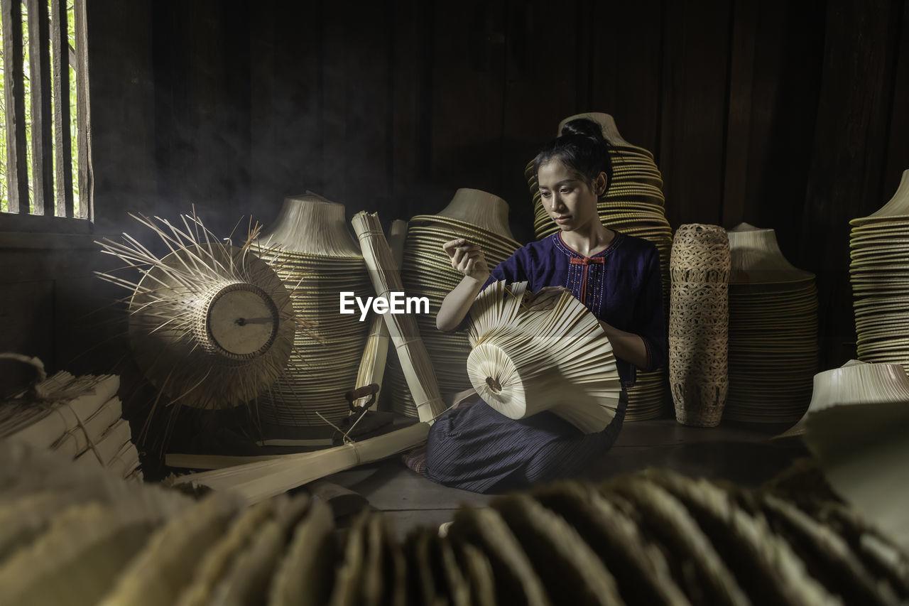 Woman weaving wicker hat in workshop