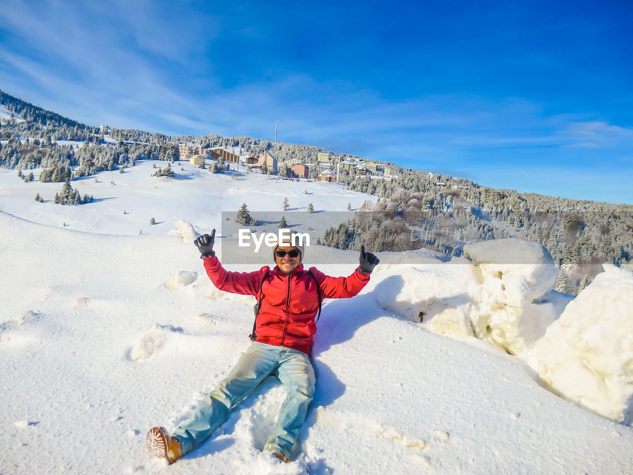 Portrait Of Man Showing Thumbs Up While Sitting On Snowcapped Mountain Against Sky