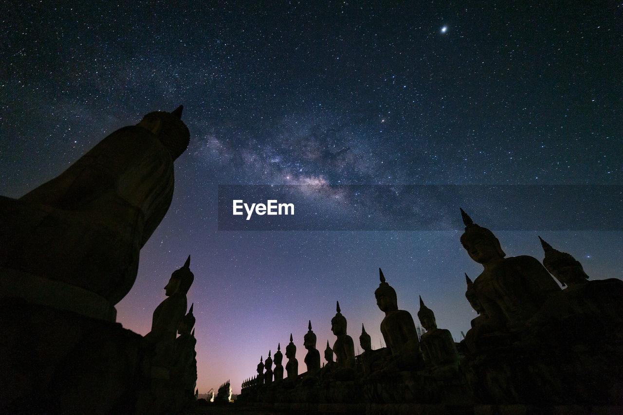 Low Angle View Of Buddha Statues Against Star Field At Night