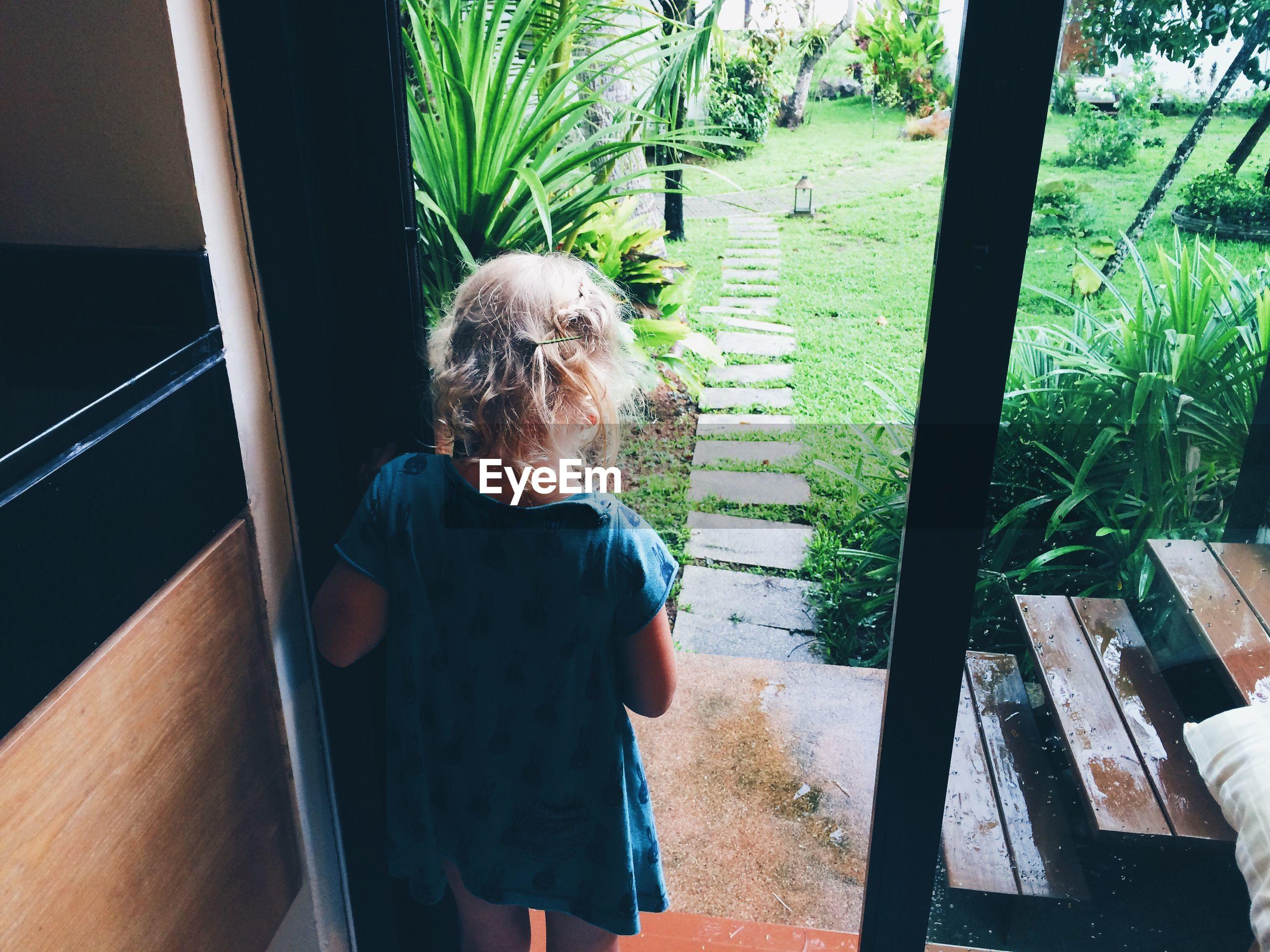 Rear view of young girl standing in doorway