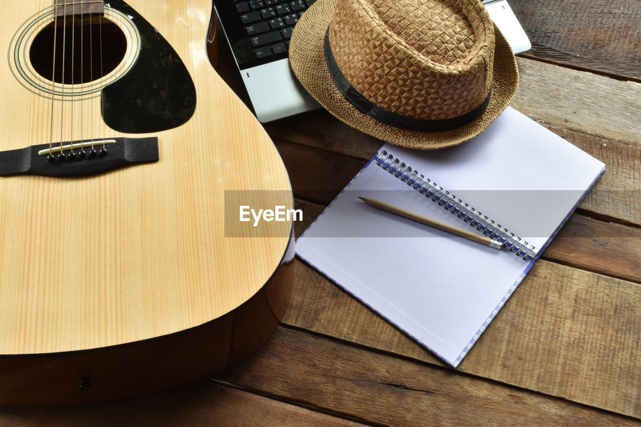 table, wood - material, high angle view, still life, hat, no people, indoors, music, brown, musical instrument, close-up, retro styled, publication, container, paper, book, musical equipment, technology, pen, personal accessory