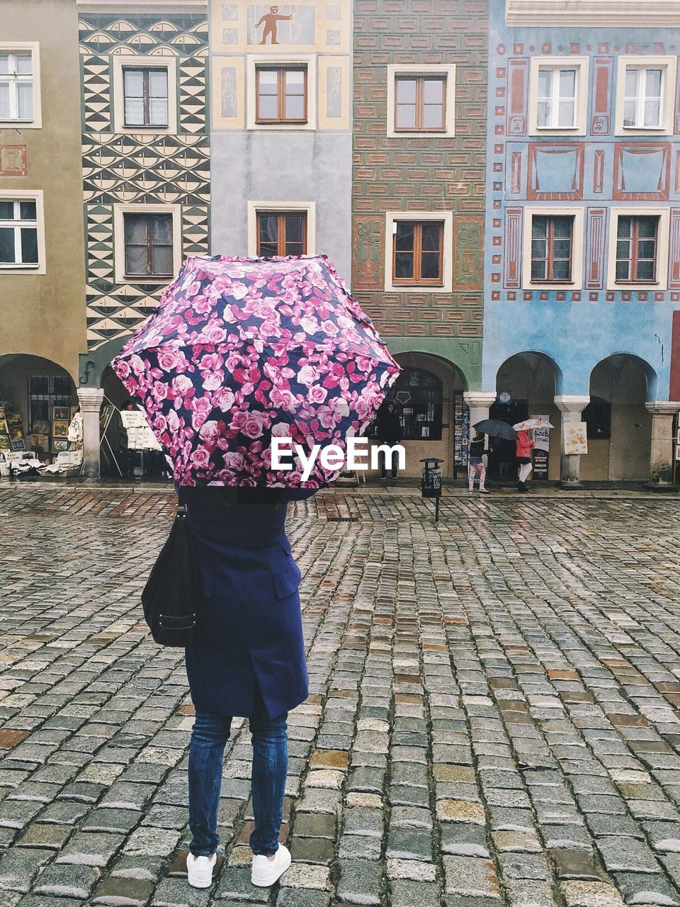 Rear view of woman with umbrella standing on street by building during rainy season