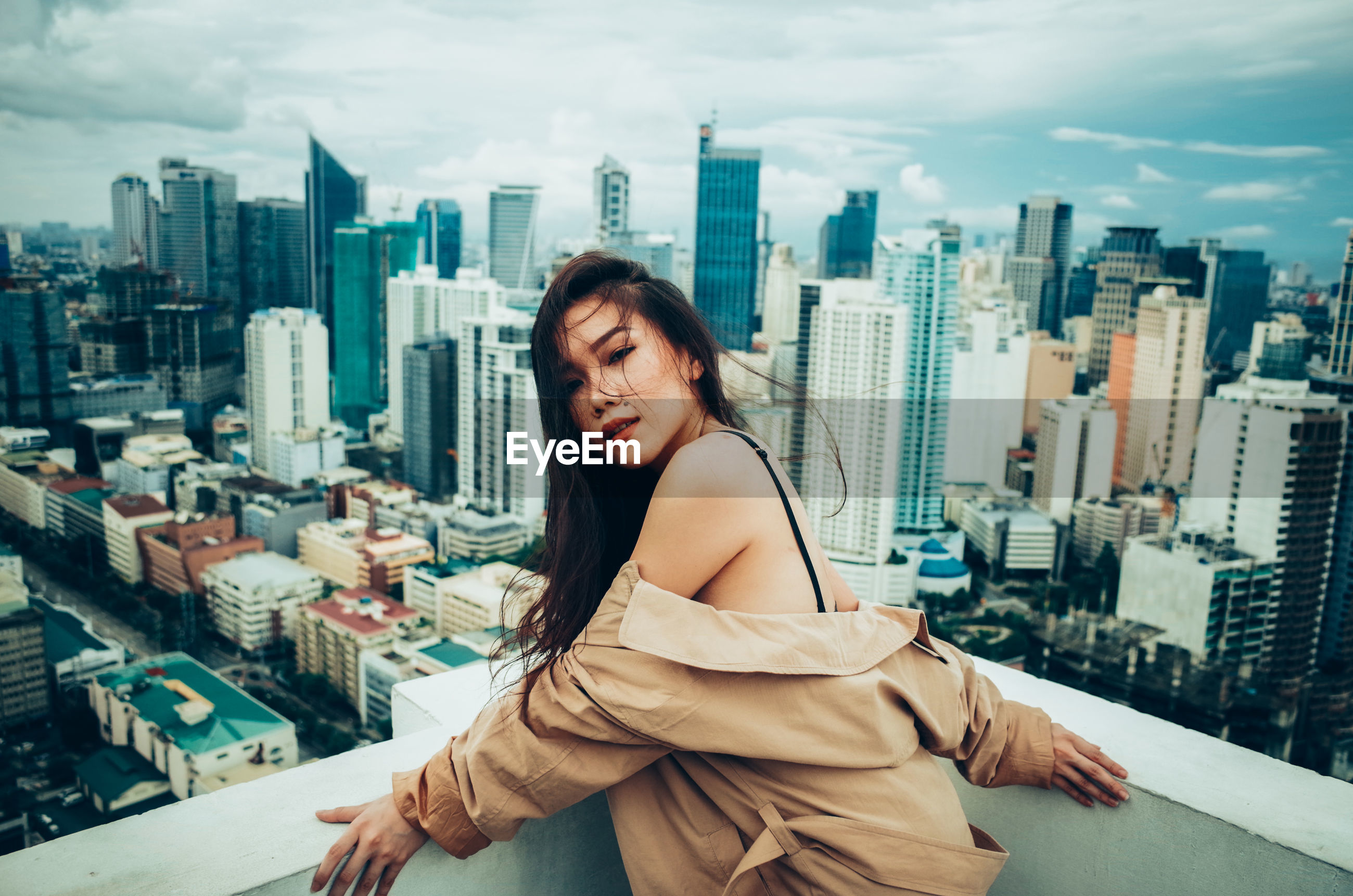BEAUTIFUL YOUNG WOMAN WITH CITYSCAPE AGAINST SKY