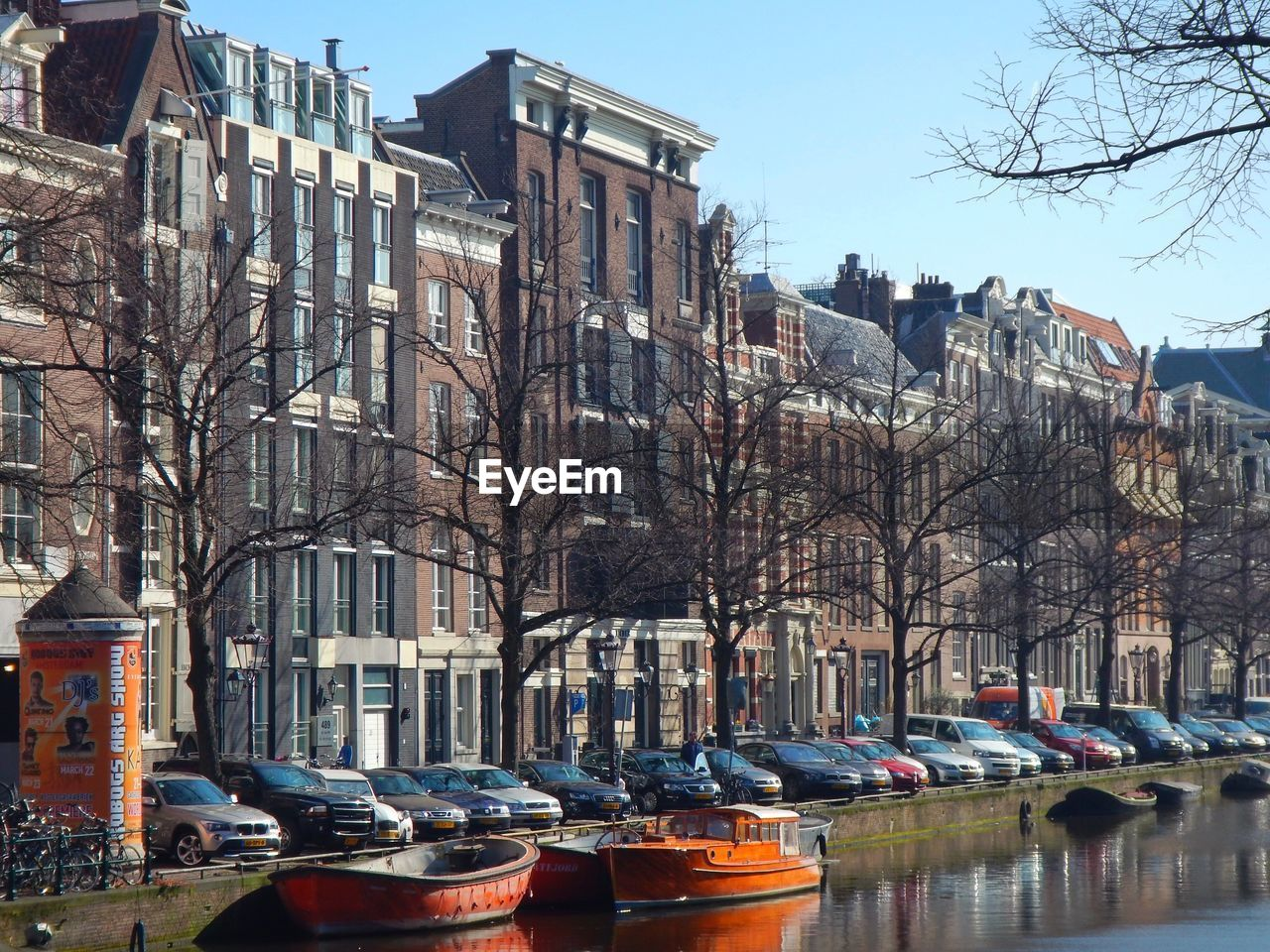 Boats moored at canal by buildings against clear sky