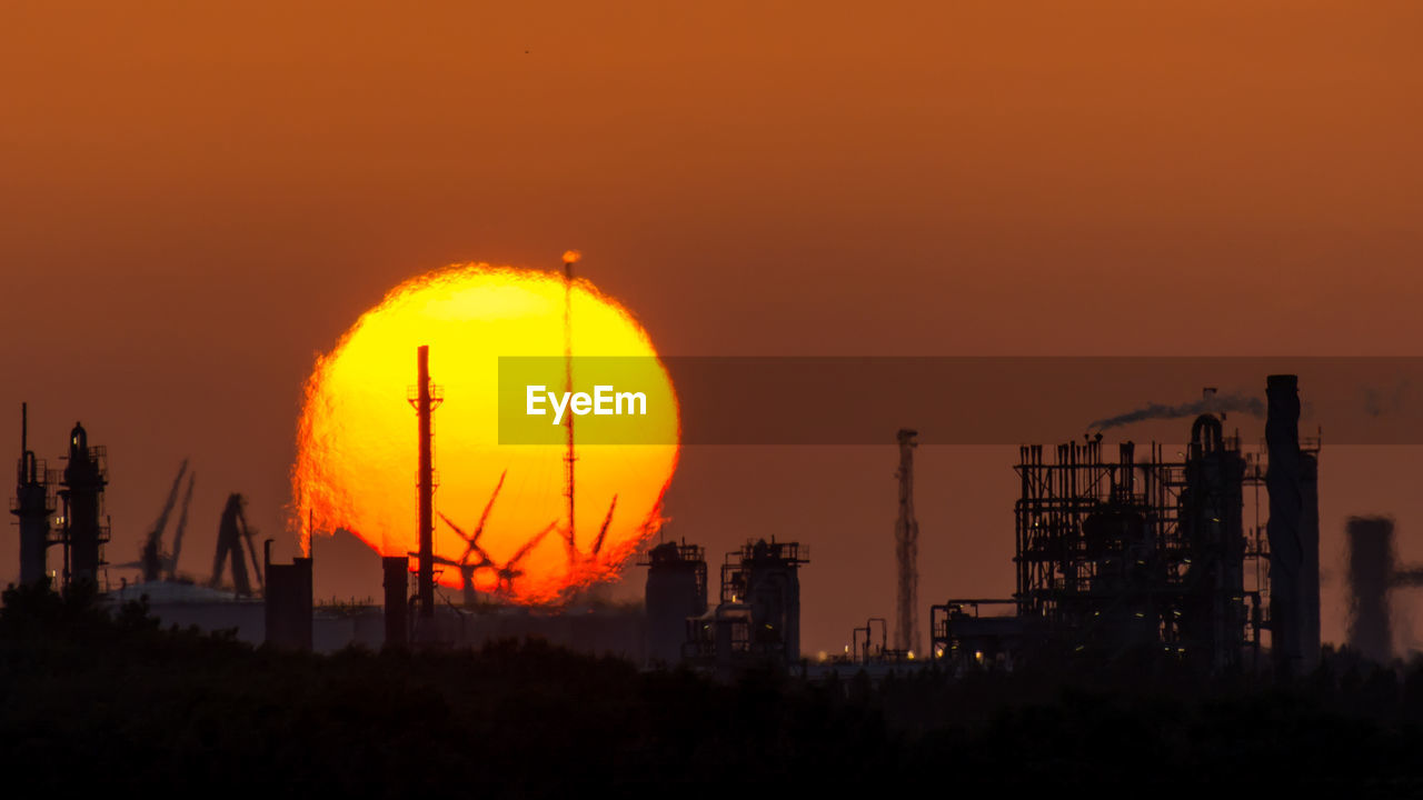 sunset, orange color, sky, building exterior, industry, sun, built structure, architecture, nature, factory, no people, fuel and power generation, silhouette, beauty in nature, outdoors, industrial building, circle, scenics - nature, environmental issues, technology, pollution, romantic sky