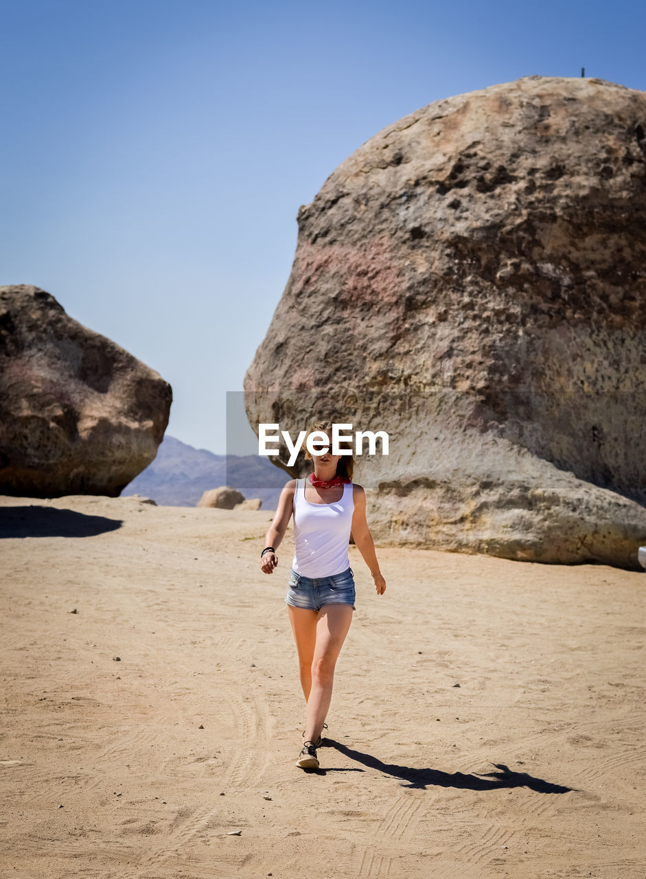 FULL LENGTH PORTRAIT OF A WOMAN ON BEACH