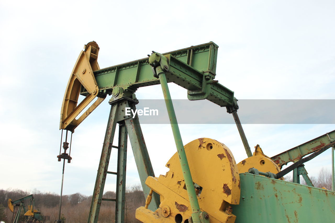 Drilling Rig On Field Against Sky