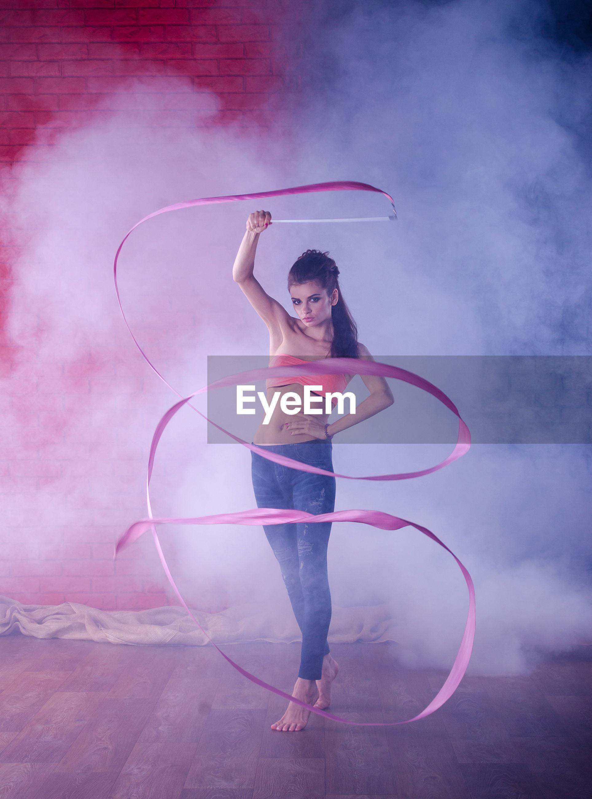 Full length of ballet dancer dancing in ballet studio