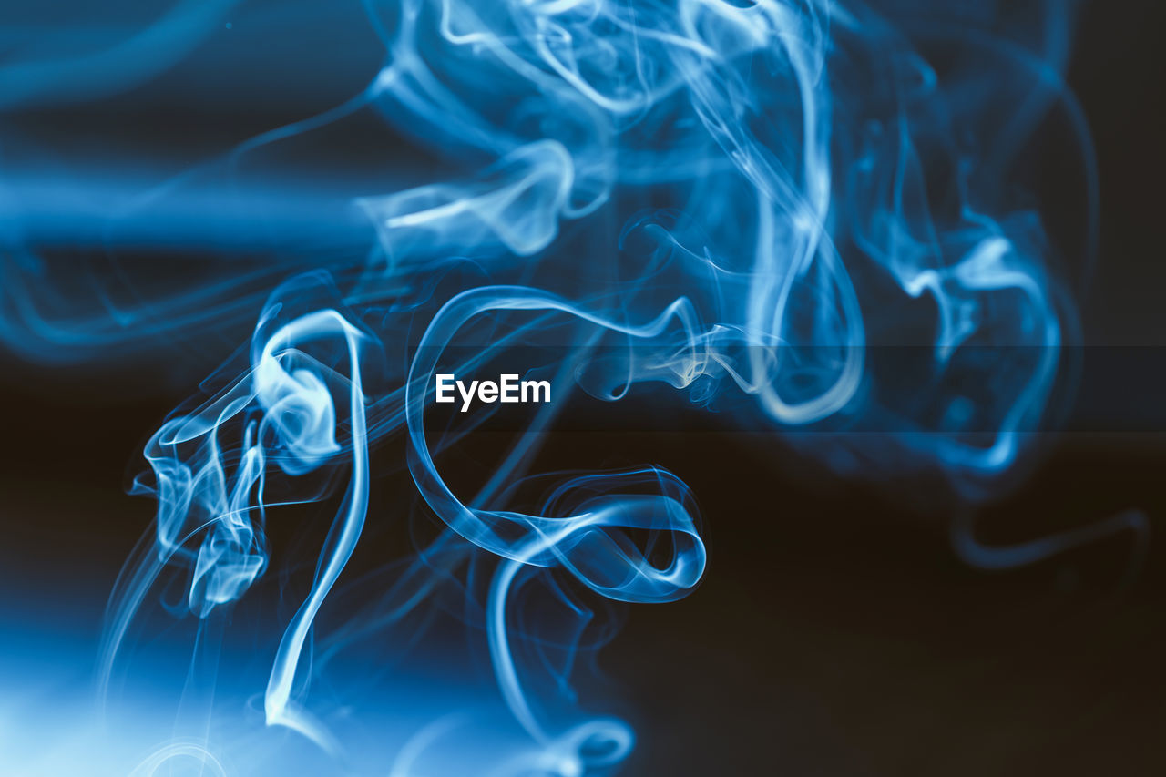 smoke - physical structure, burning, no people, close-up, swirl, indoors, pattern, motion, blue, abstract, studio shot, glowing, incense, illuminated, white color, changing form, flame, natural pattern, design, heat - temperature, black background