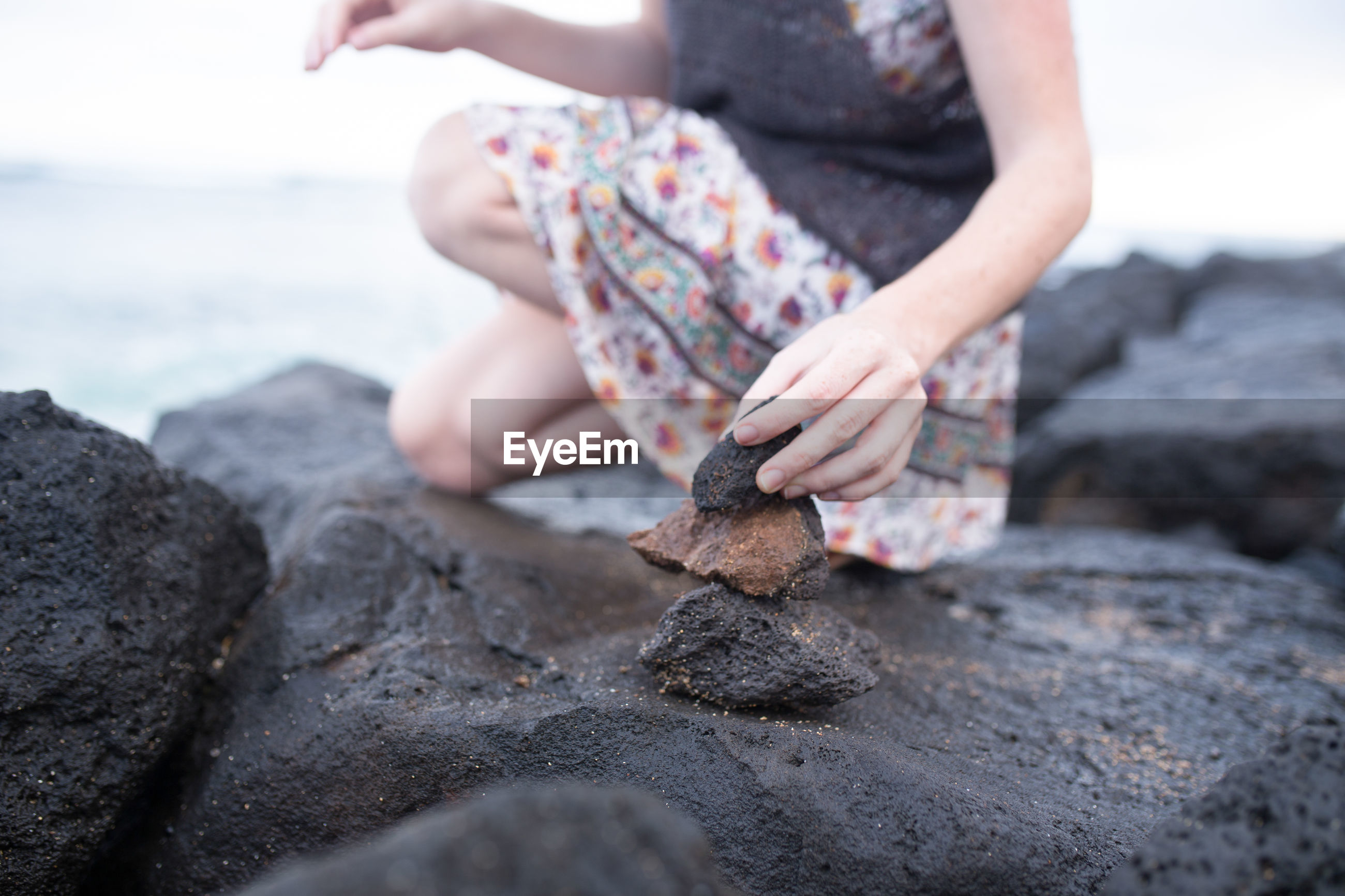 Low section of woman crouching on rock at beach