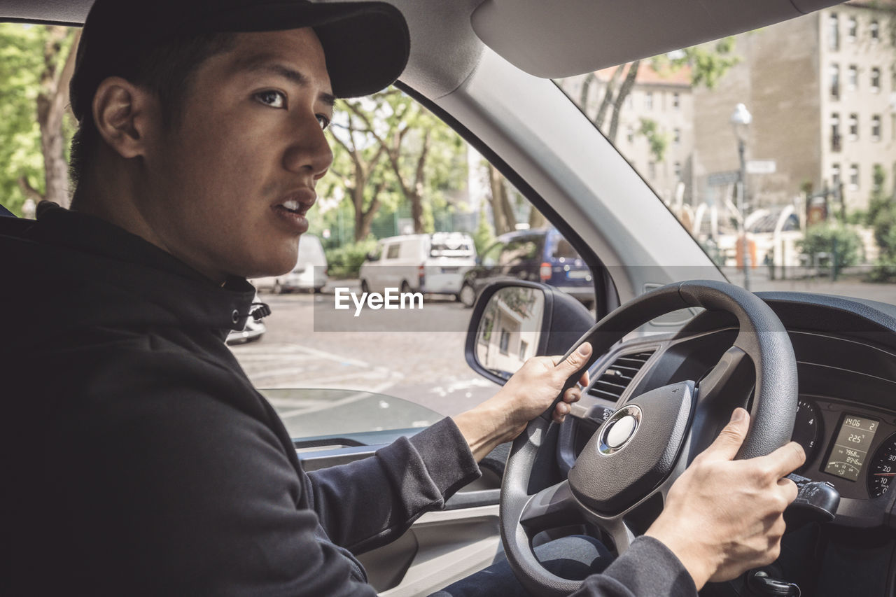 SIDE VIEW PORTRAIT OF MAN SITTING IN CAR