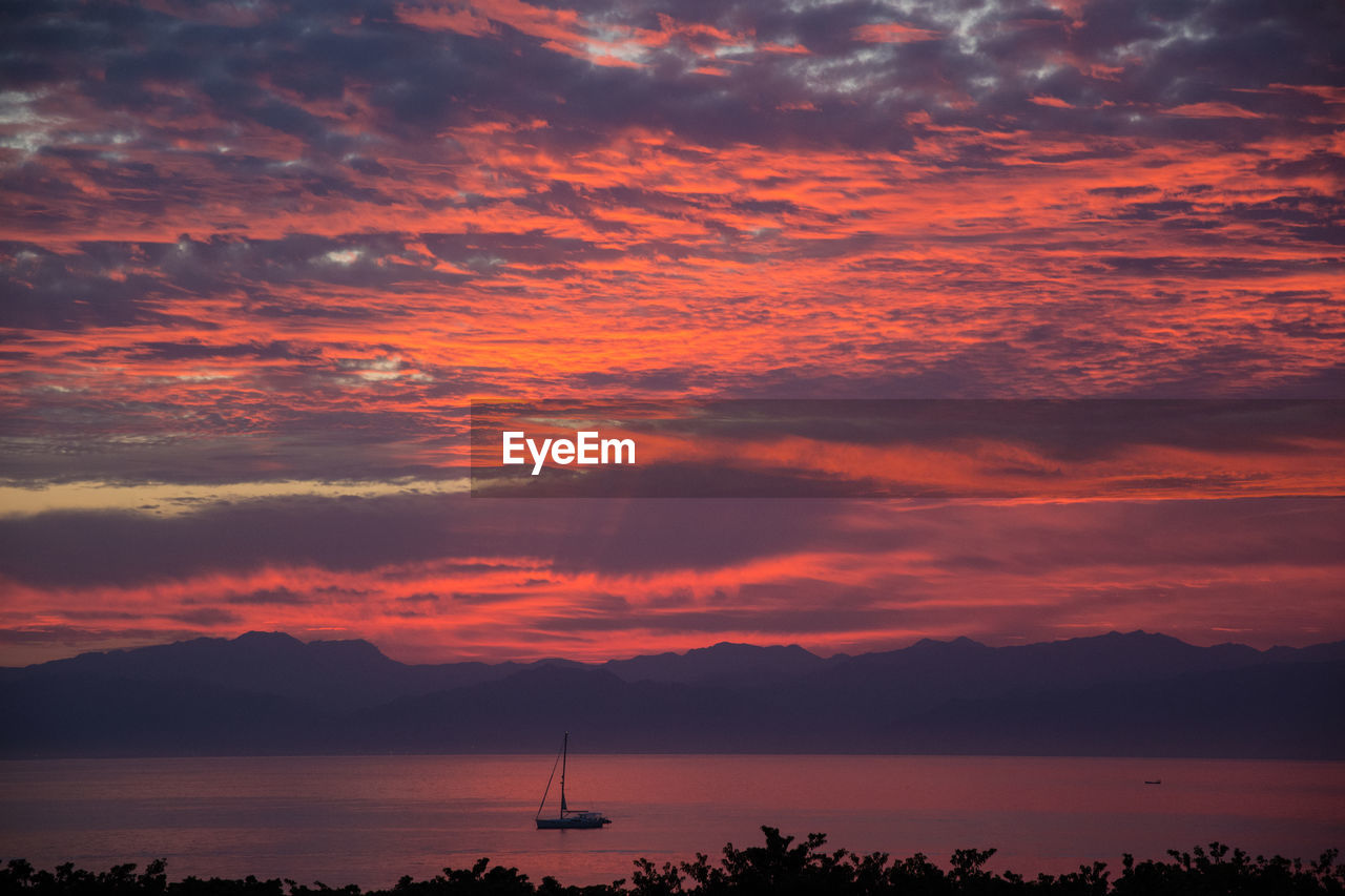 sky, cloud - sky, sunset, beauty in nature, scenics - nature, water, tranquility, tranquil scene, silhouette, orange color, nature, sea, idyllic, no people, dramatic sky, mountain, non-urban scene, outdoors, waterfront, sailboat