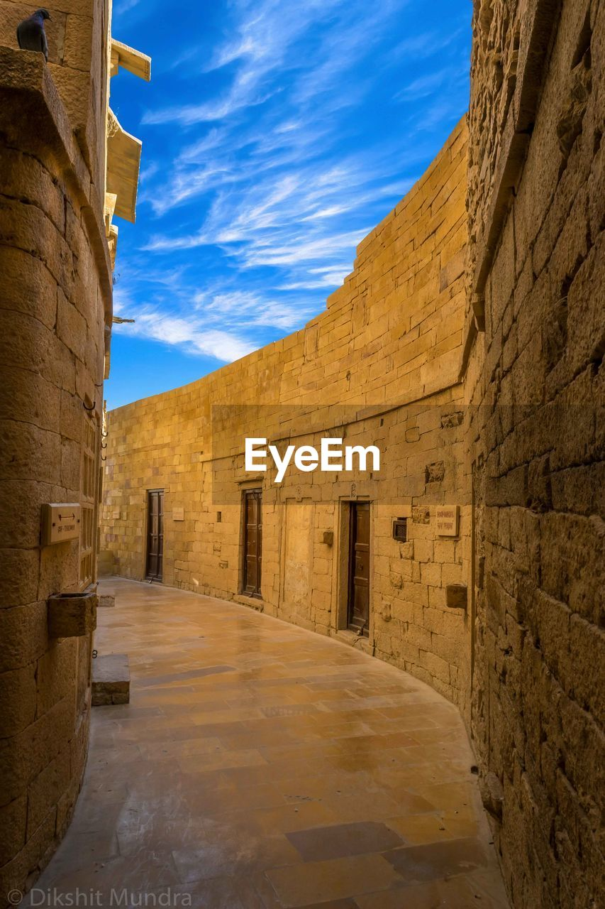 architecture, built structure, history, the past, sky, building exterior, ancient, building, no people, cloud - sky, nature, direction, the way forward, travel destinations, wall - building feature, wall, day, old, arch, old ruin, ancient civilization, outdoors, stone wall, alley, archaeology, ancient history