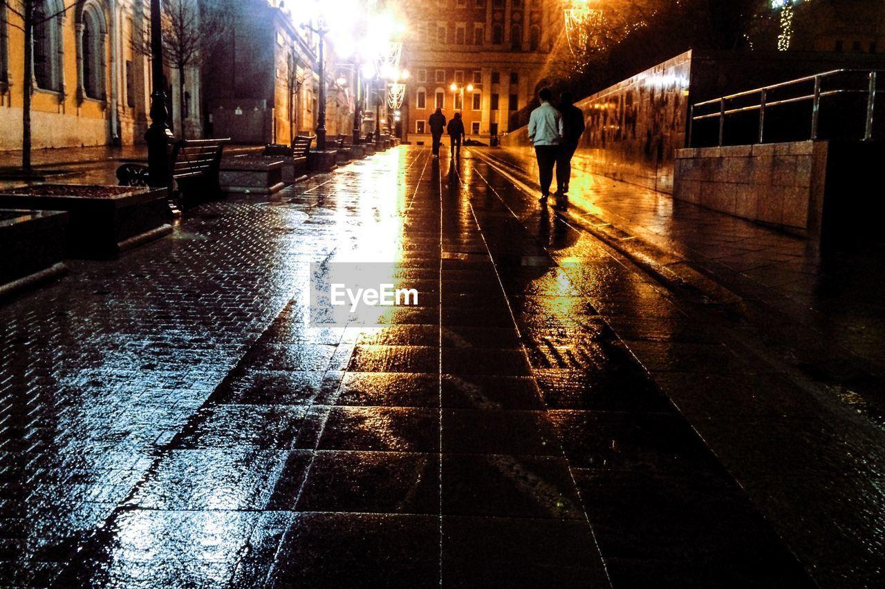 People Walking On Wet Illuminated Street At Night
