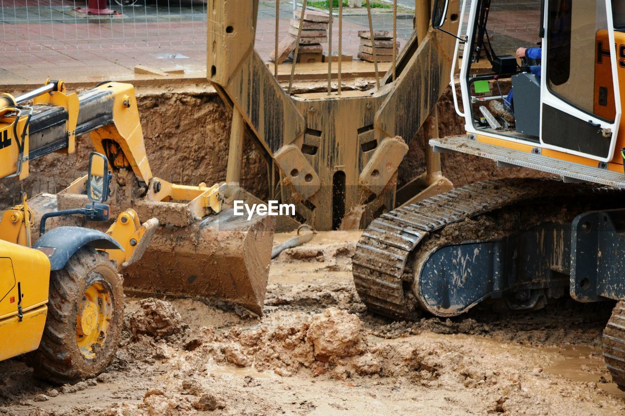 A yellow digger excavating mud and one crane bucket picking up