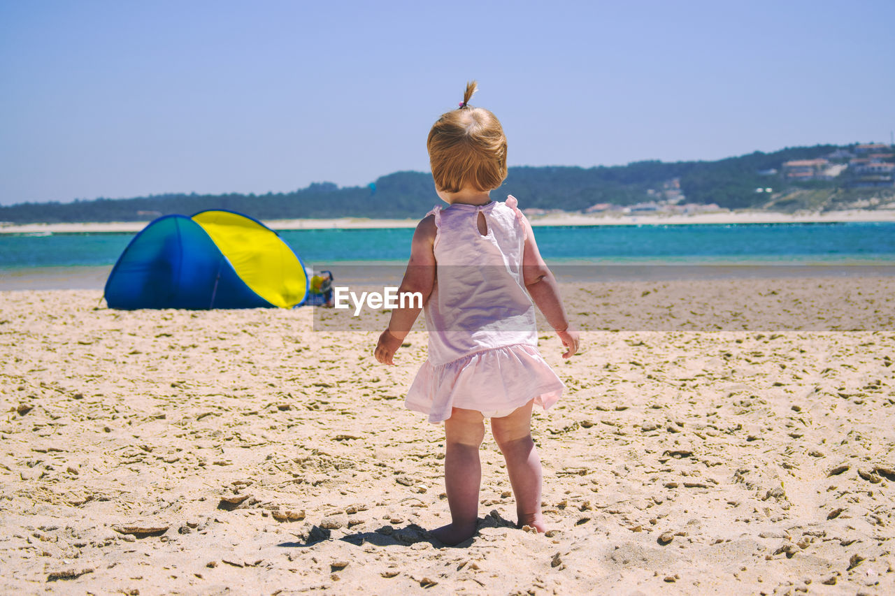 real people, beach, one person, rear view, leisure activity, sea, full length, day, lifestyles, sand, nature, outdoors, vacations, water, childhood, beauty in nature, sunlight, standing, blue, clear sky, scenics, sky, people