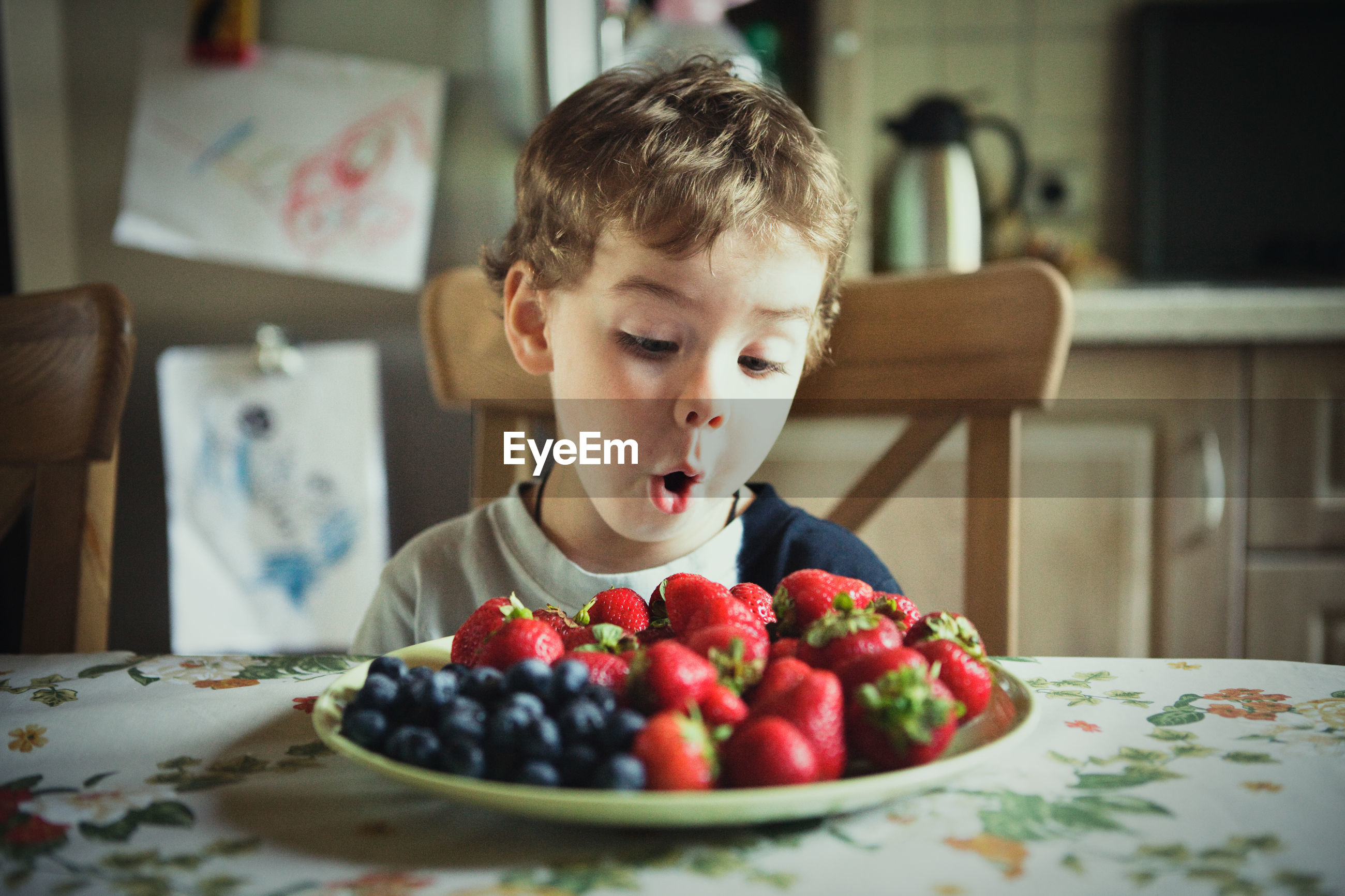 Cute boy looking at fruits in plate at table