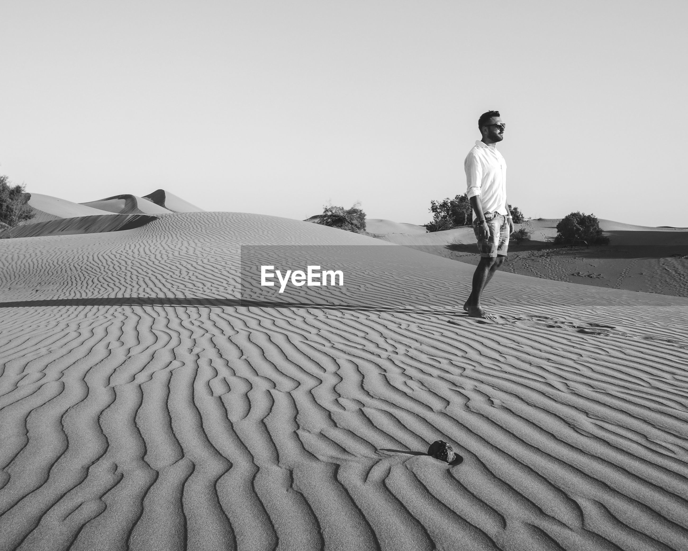Man standing on sand against clear sky