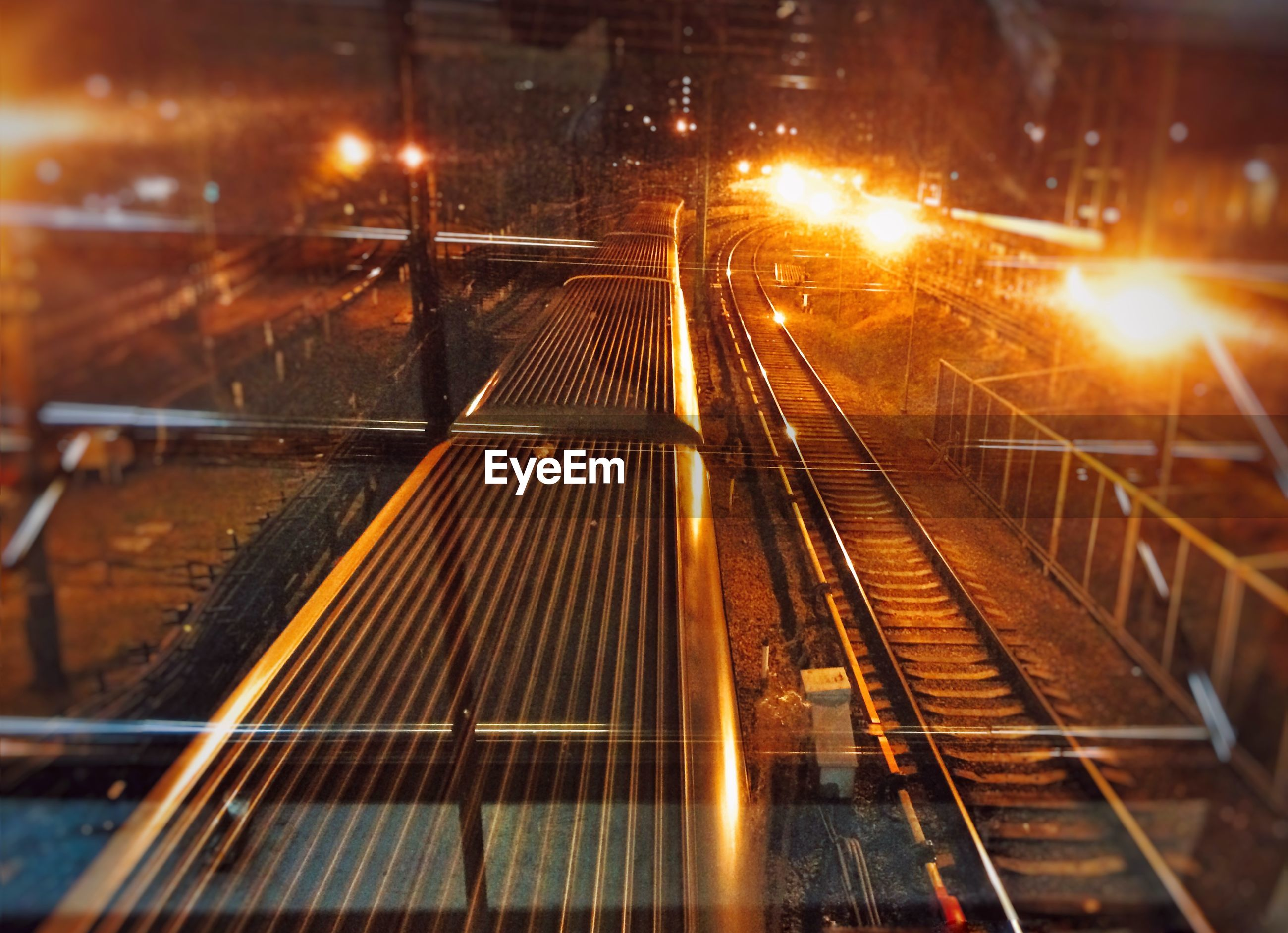 railroad track, transportation, the way forward, rail transportation, illuminated, diminishing perspective, vanishing point, connection, built structure, high angle view, metal, railing, architecture, railway track, public transportation, night, railroad station, bridge - man made structure, railroad station platform, mode of transport