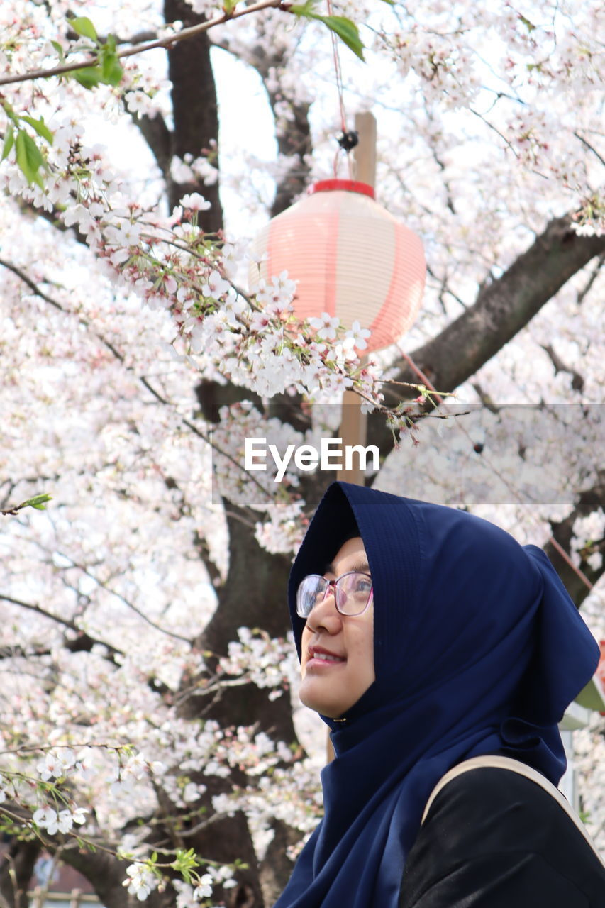 tree, plant, one person, real people, flowering plant, flower, nature, day, growth, blossom, portrait, standing, lifestyles, young adult, fragility, springtime, smiling, leisure activity, outdoors, cherry blossom, cherry tree