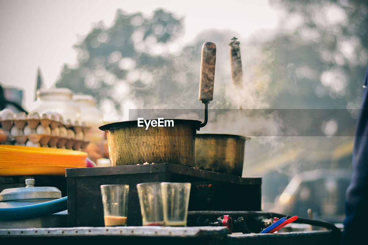 Close-up of steam emitting from utensils on stove