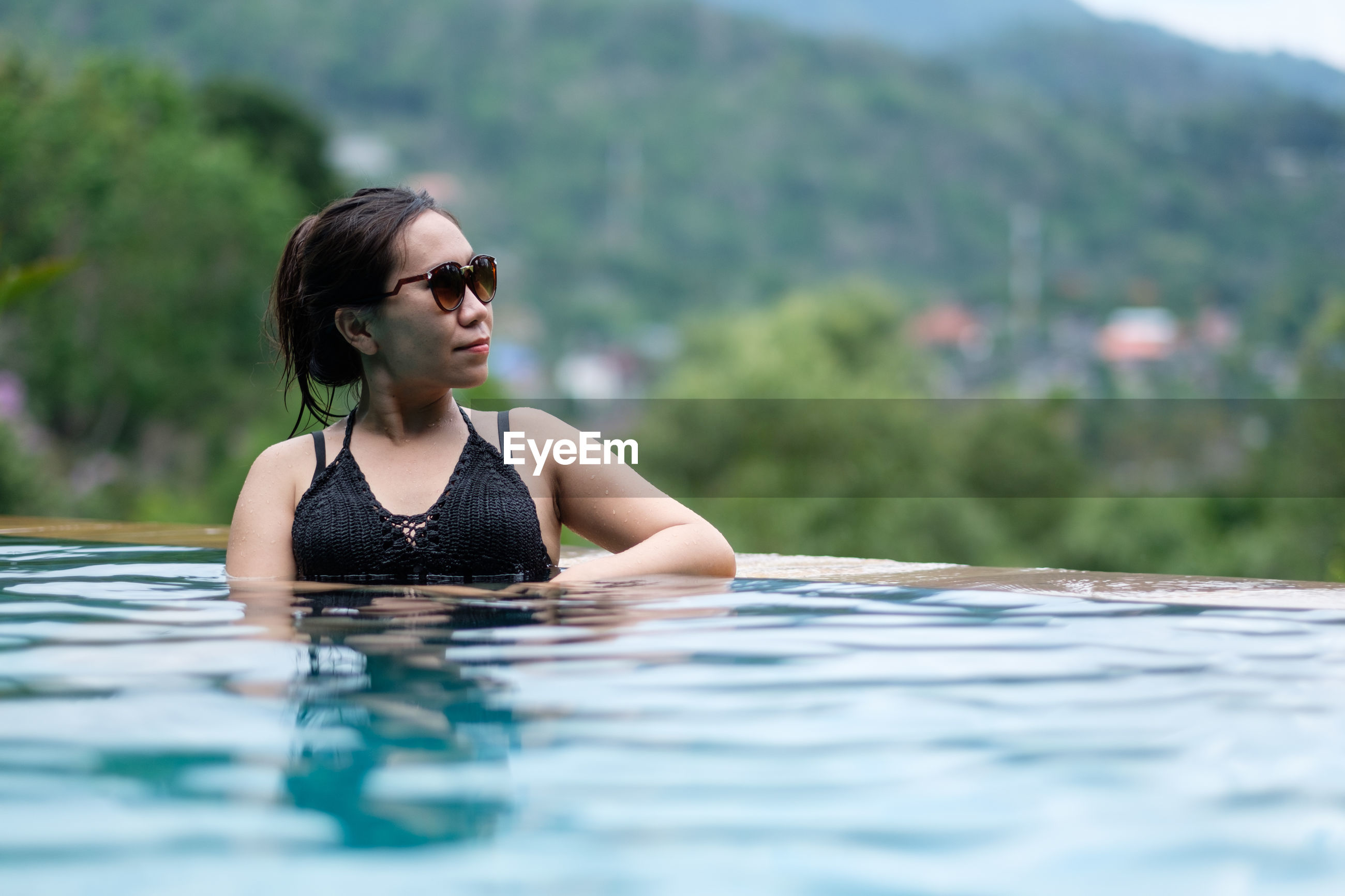 Young woman wearing sunglasses looking away in swimming pool