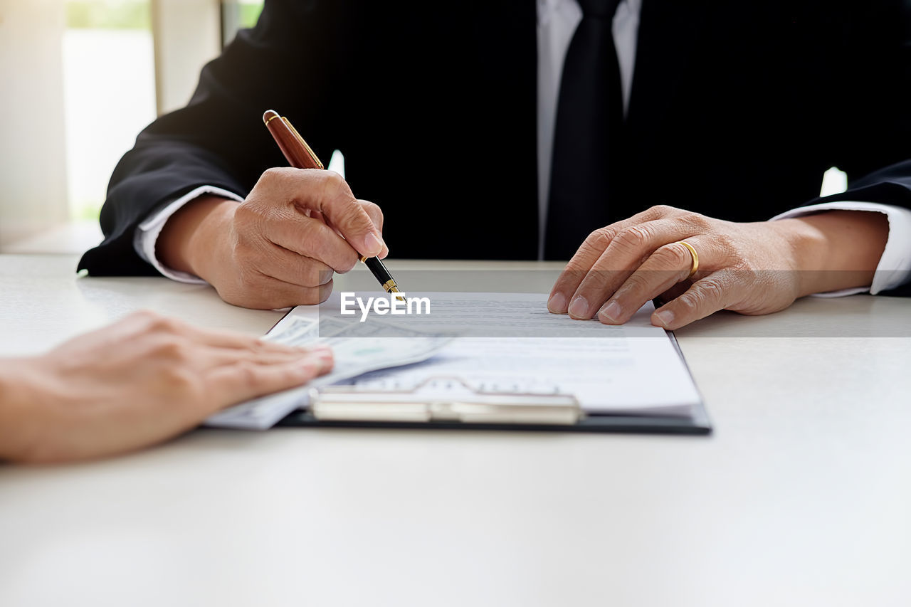 writing, human hand, pen, men, table, real people, indoors, desk, midsection, sitting, human body part, holding, businessman, one person, well-dressed, paper, close-up, day