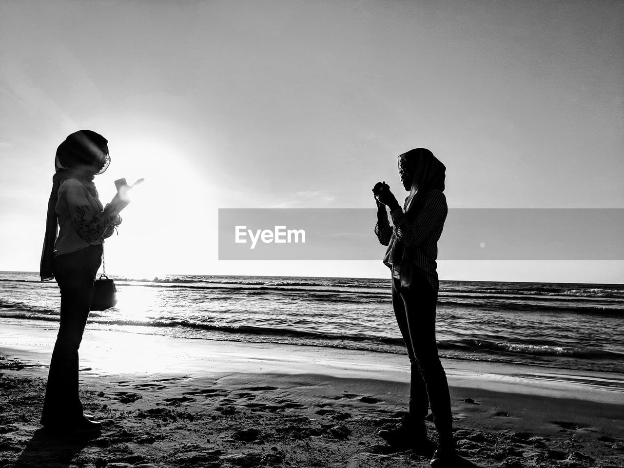 Girl photographing friend using mobile phone while standing at beach against sky