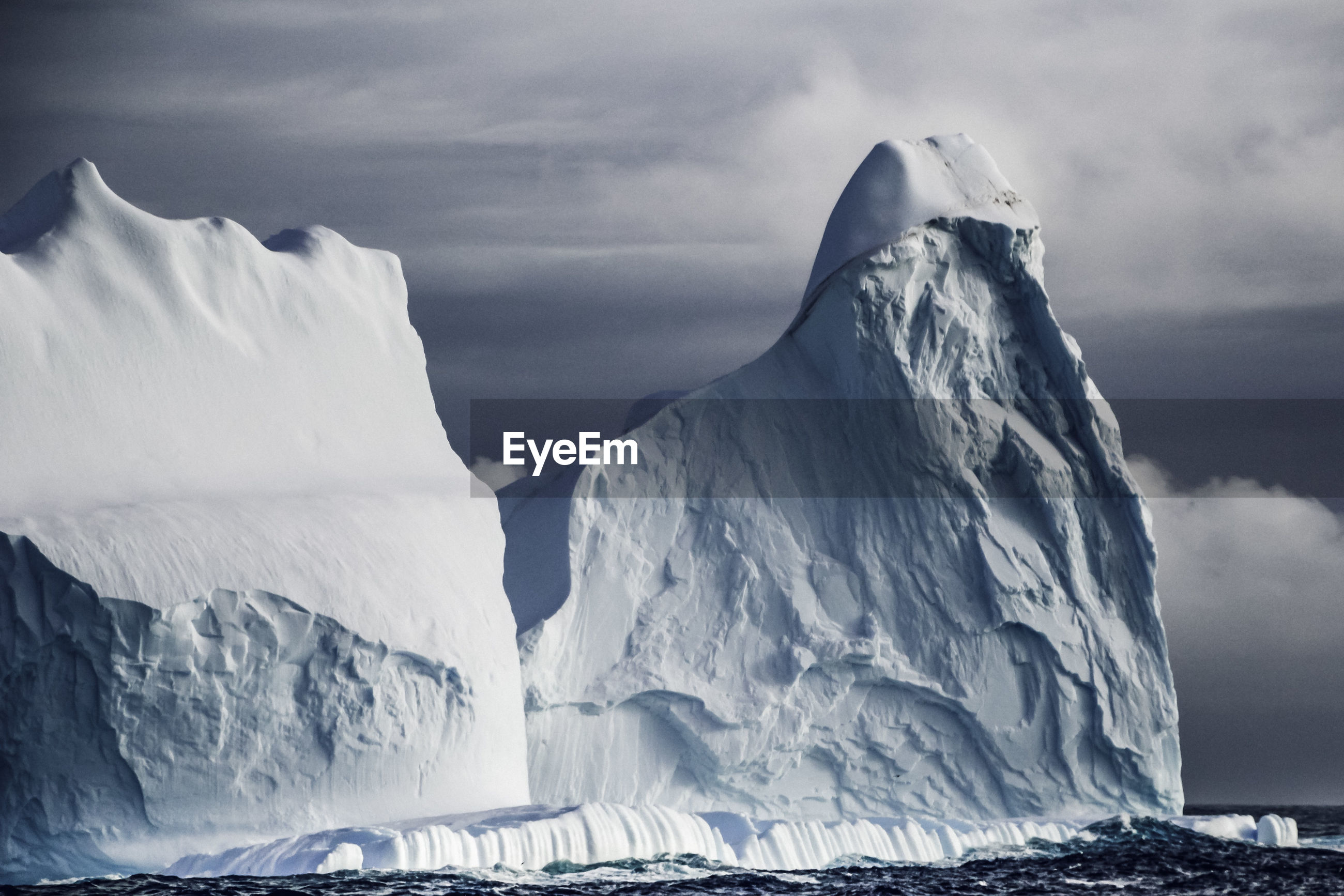 Scenic view of icebergs against cloudy sky