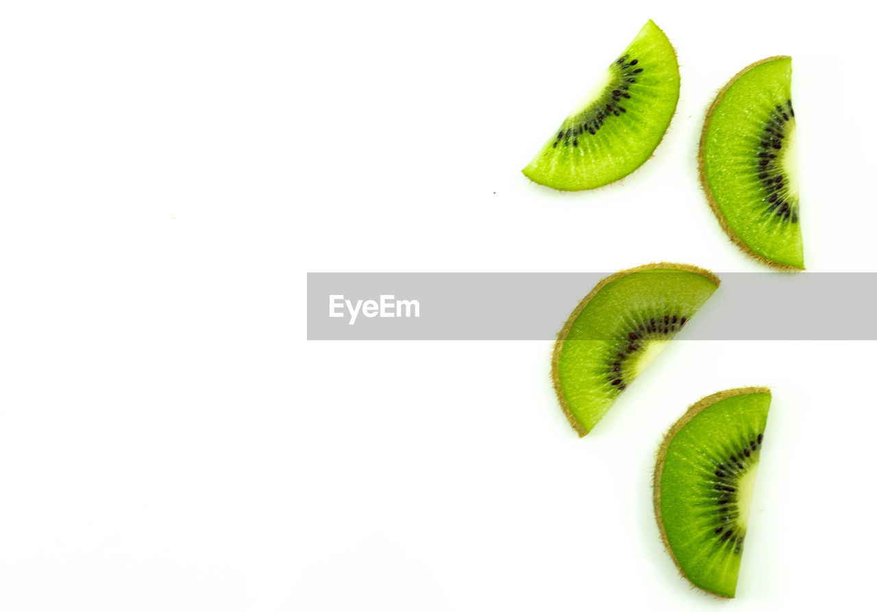 kiwi, healthy eating, studio shot, wellbeing, white background, freshness, food, slice, food and drink, kiwi - fruit, fruit, indoors, copy space, green color, no people, cross section, still life, close-up, cut out, group of objects, ripe