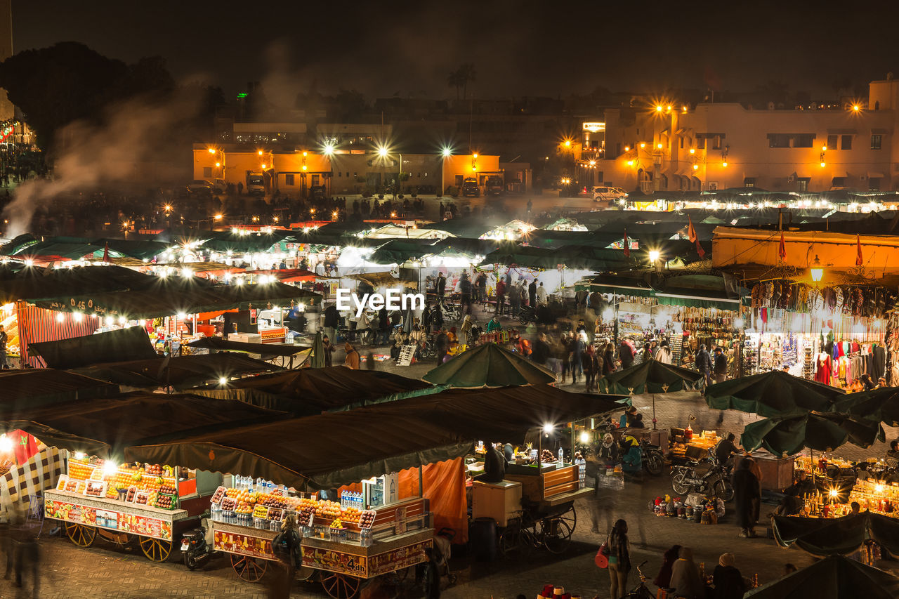 illuminated, night, market, architecture, built structure, market stall, building exterior, business, retail, city, crowd, lighting equipment, high angle view, group of people, large group of people, real people, small business, for sale, women, water, street market, buying, outdoors, sale, consumerism
